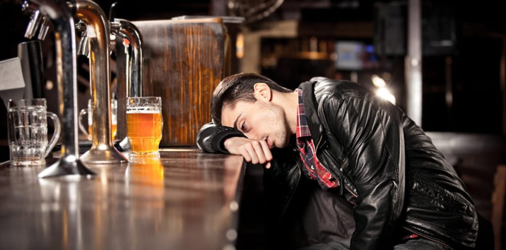 intoxicated man lays his head on a bar while staring at his current mug of beer