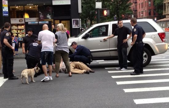 pedestrians, cops and driver stand around an SUV after an accident